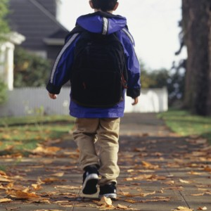 Boy walking along leaf-covered path, wearing jacket and backpack