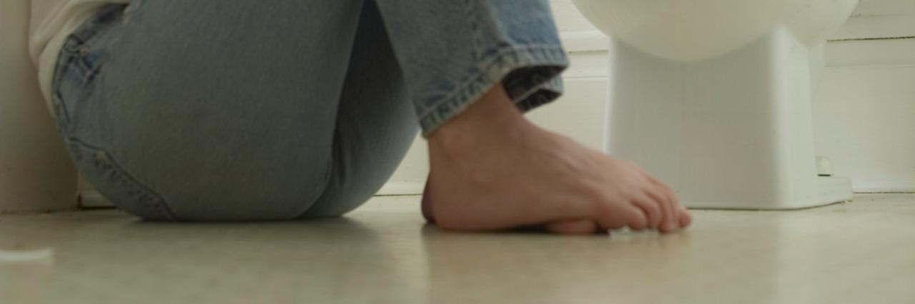 woman on bathroom floor by toilet hugging knees