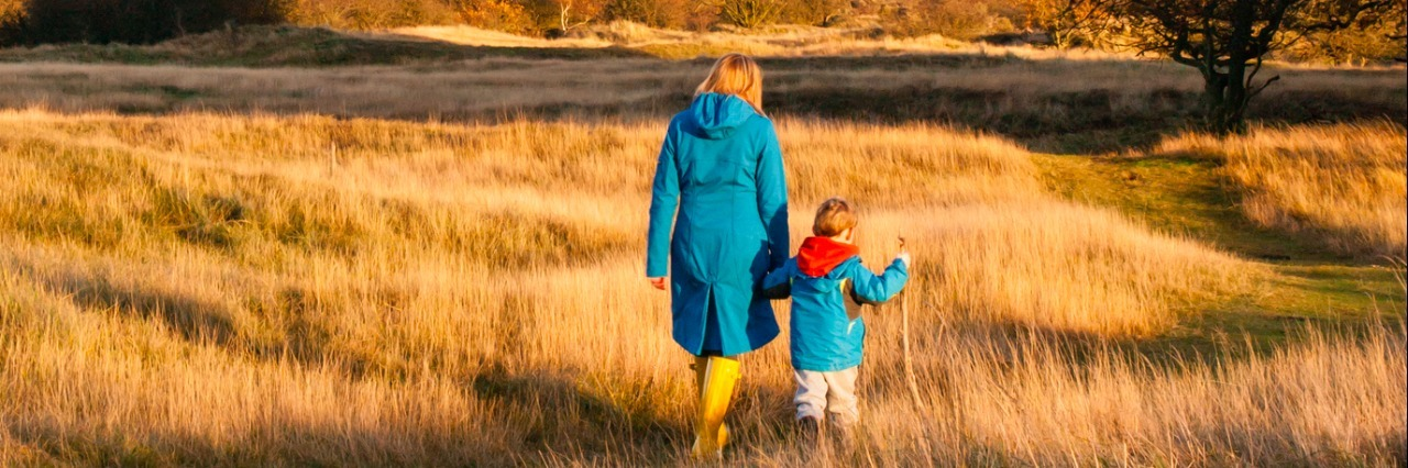 woman and boy walk hand in hand in a sunny autumn landscape