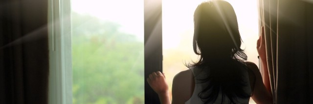 woman looking out window at sunlight