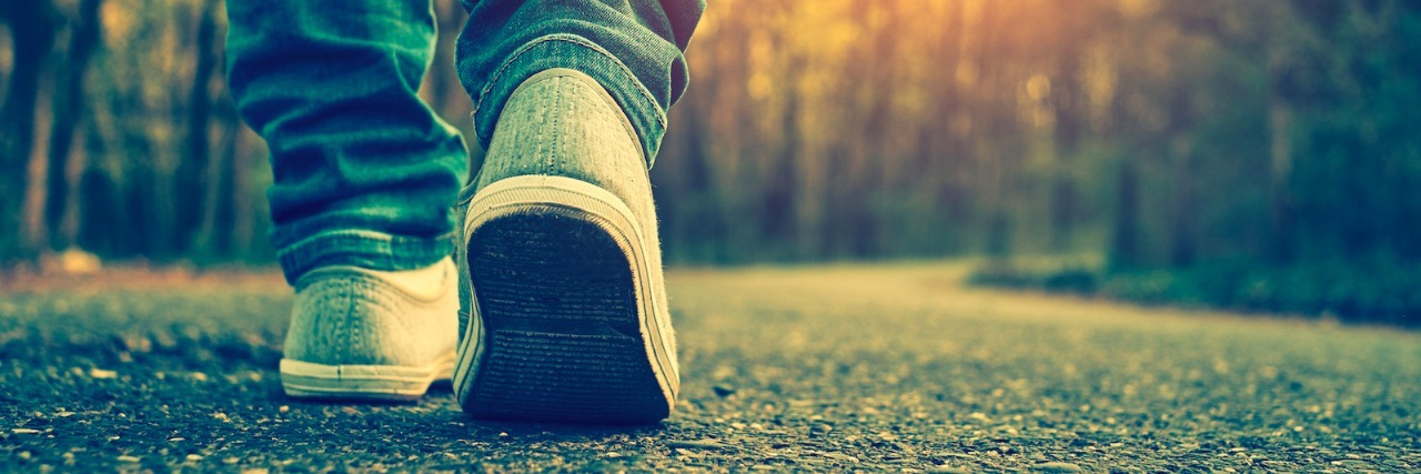 Close-up of person wearing jeans and shoes, walking on tree-lined road