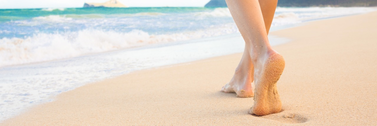 woman walks on beach toward ocean