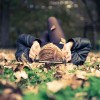 woman with her headphones in laying in a pile of leaves