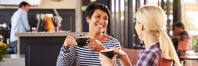 two female friends chatting and drinking coffee