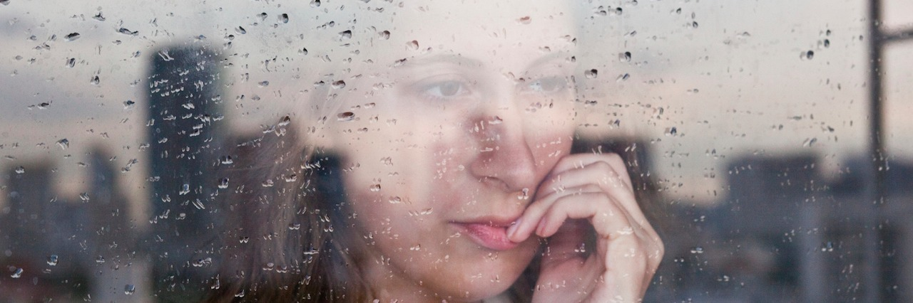 A woman looking at her window on a rainy day