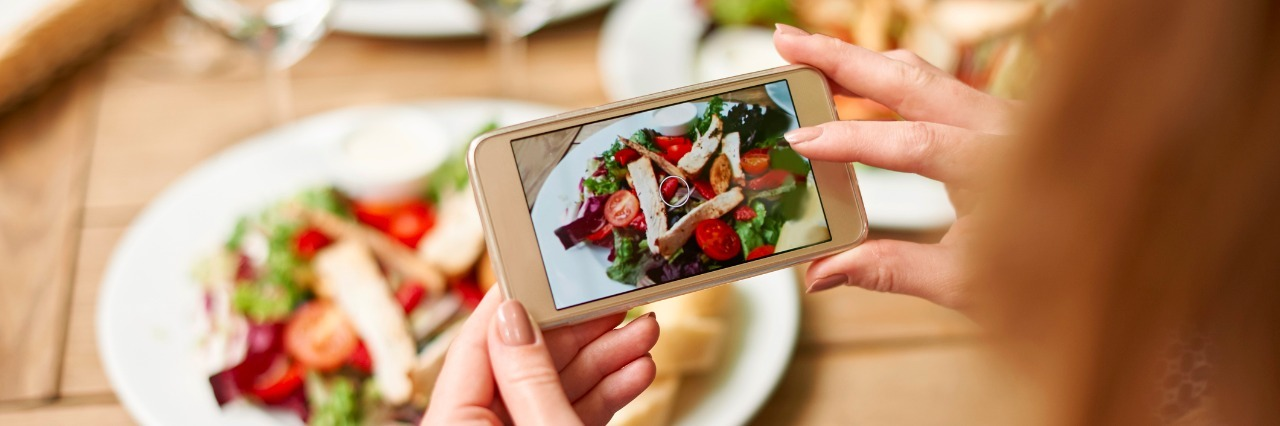 a woman taking a picture of her salad with her phone camera