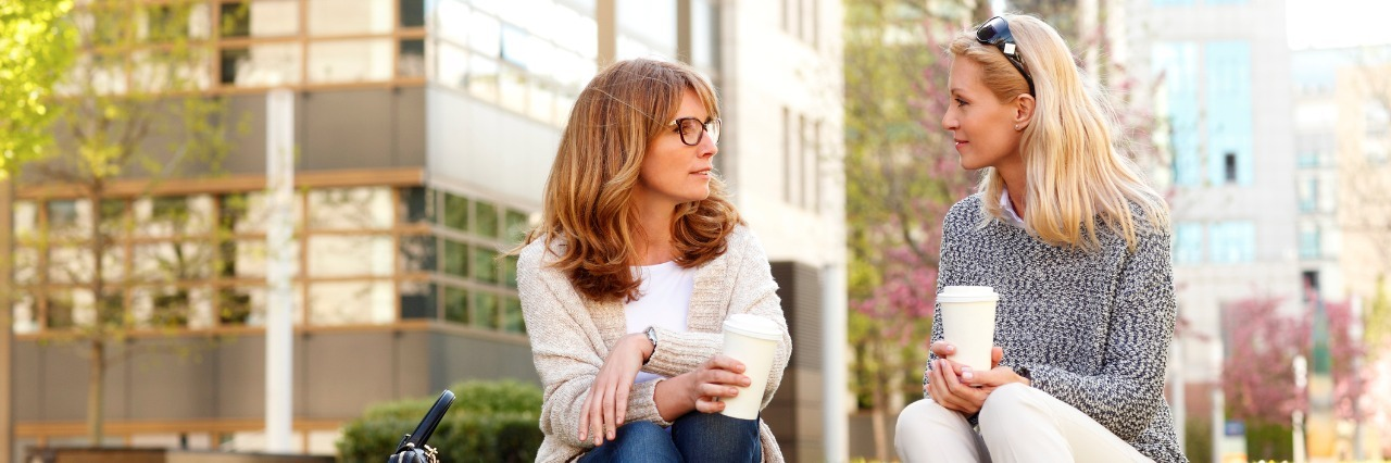 two women sitting outside holding coffee and having a discussion