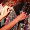 woman's hands looking at shirts hanging on rack