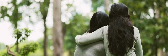 two women sitting outside in a park hugging