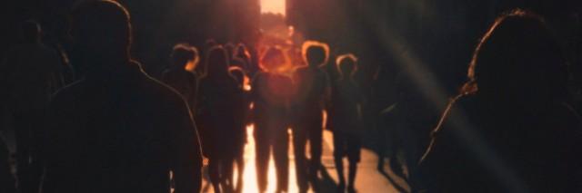 group of people walking towards light