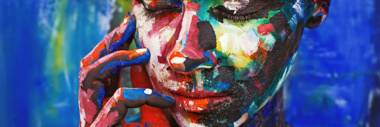 Living painting - young woman completely covered with thick paint