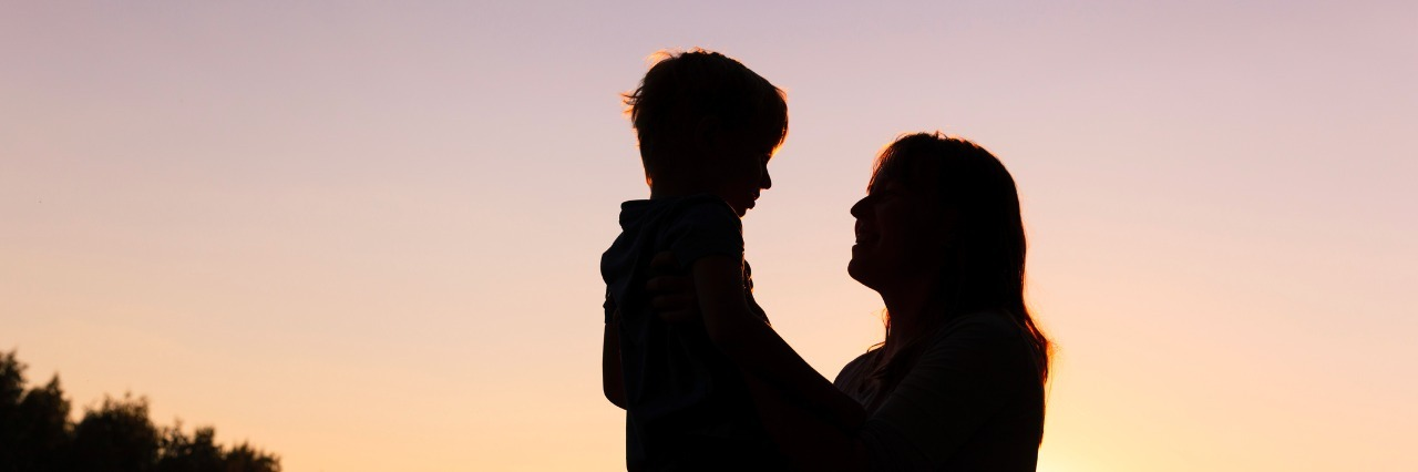 happy loving mother and little son at sunset
