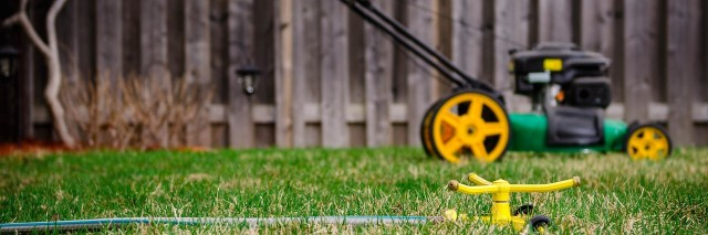 lawnmower and a sprinkler in a backyard