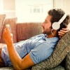 man lying on couch listening to music through headphones