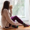 young woman sitting by the window having hot drink