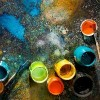 table splattered with paint cans and paint brushes