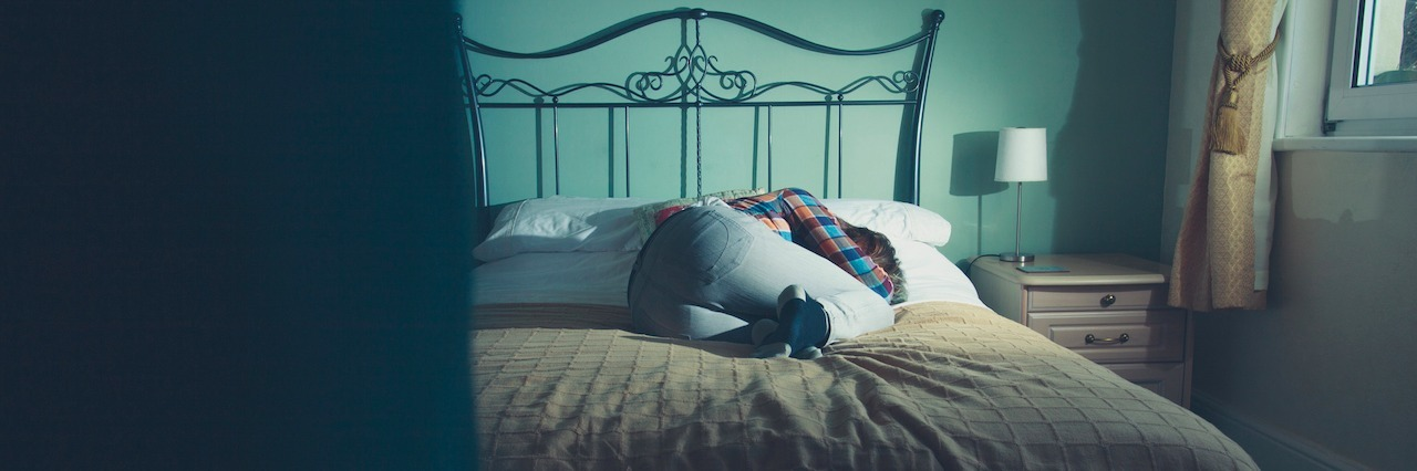 A woman laying in bed fully dressed