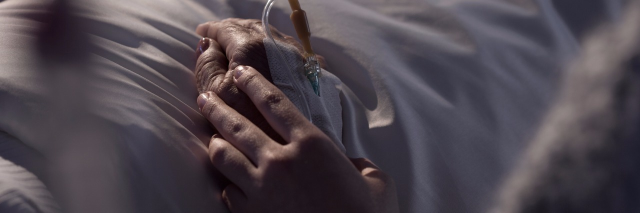 woman supporting dying mother in hospital bed