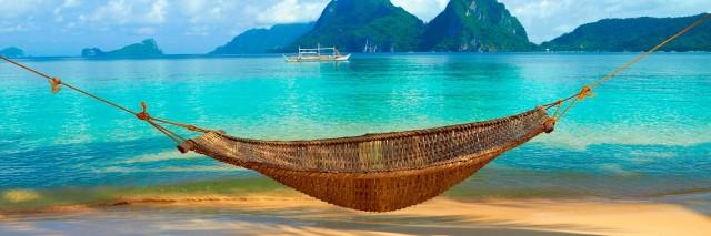 a hammock on a beach on a tropic island