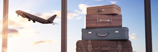 a stack of suitcases in front of a window where you can see a plane taking off