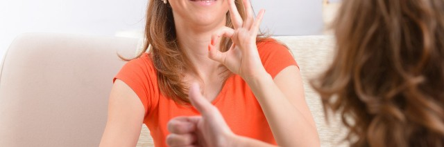 Smiling woman learning sign language.