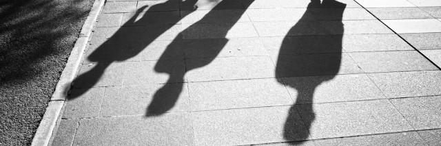 three shadows of people walking down street