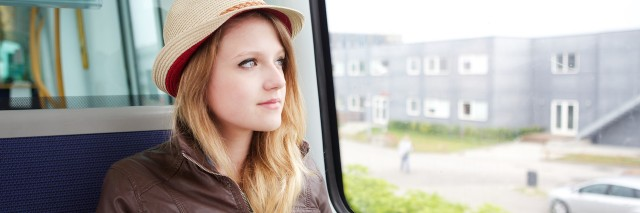 woman looking out her window on a bus