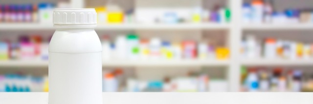 Blank white medicine bottle on counter with pharmacy drugstore