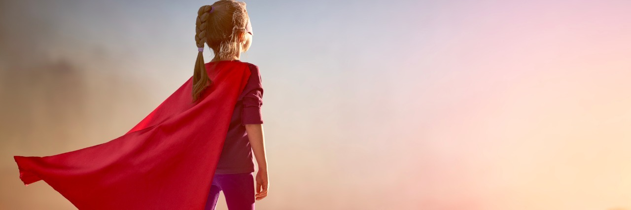 girl standing on building wearing a red superhero cape