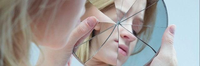 a young woman looking at herself in a cracked mirror