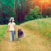 Little girl walking with a dog in a dirt road