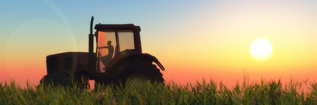 a tractor riding through a wheat field at sunset