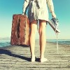 woman standing on a dock holding her shoes and a suitcase