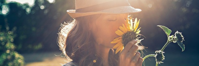 A girl smelling a sunflower.