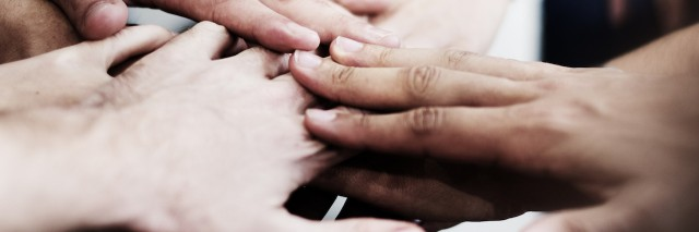 a group of people with their hands together.