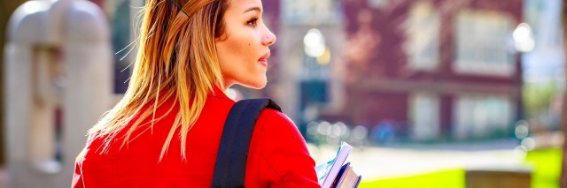 college student walking through campus with books and her backpack