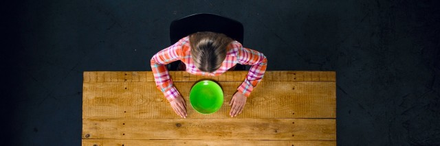 top view of girl sitting at table with an empty green plate