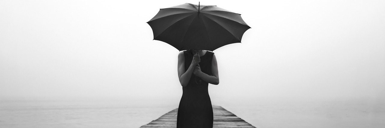 woman holding an umbrella on a dock
