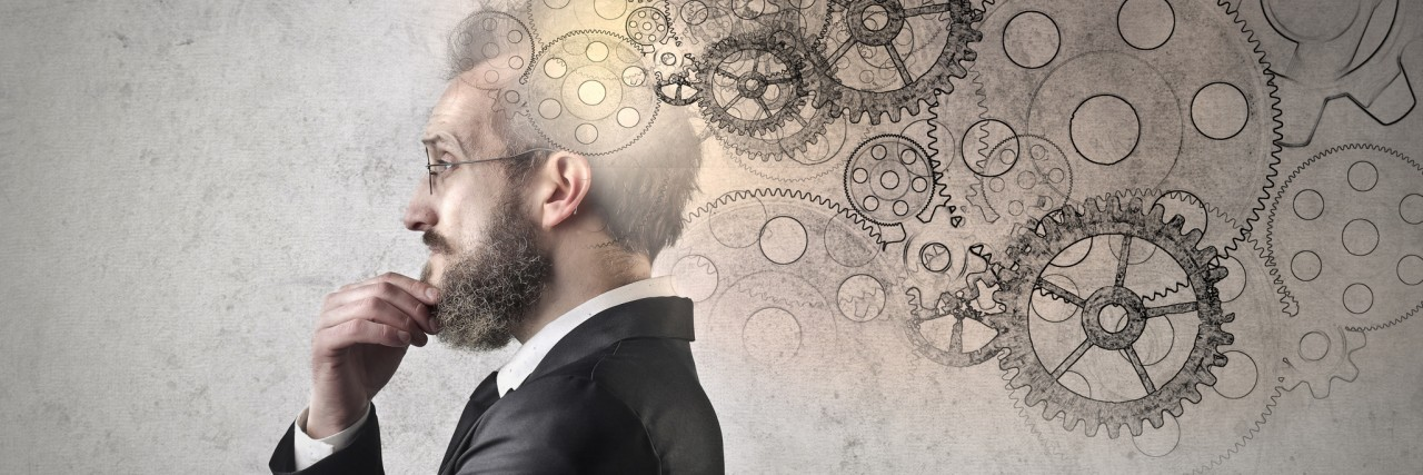 man thinking hard with wheels coming out of his head