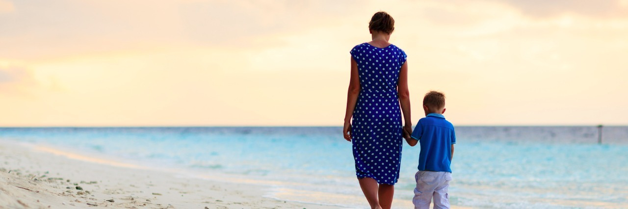 Mother and son walking on a beach at sunset