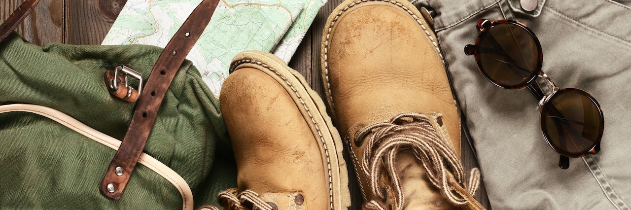hiking boots, a backpack and a map placed on a wooden floor