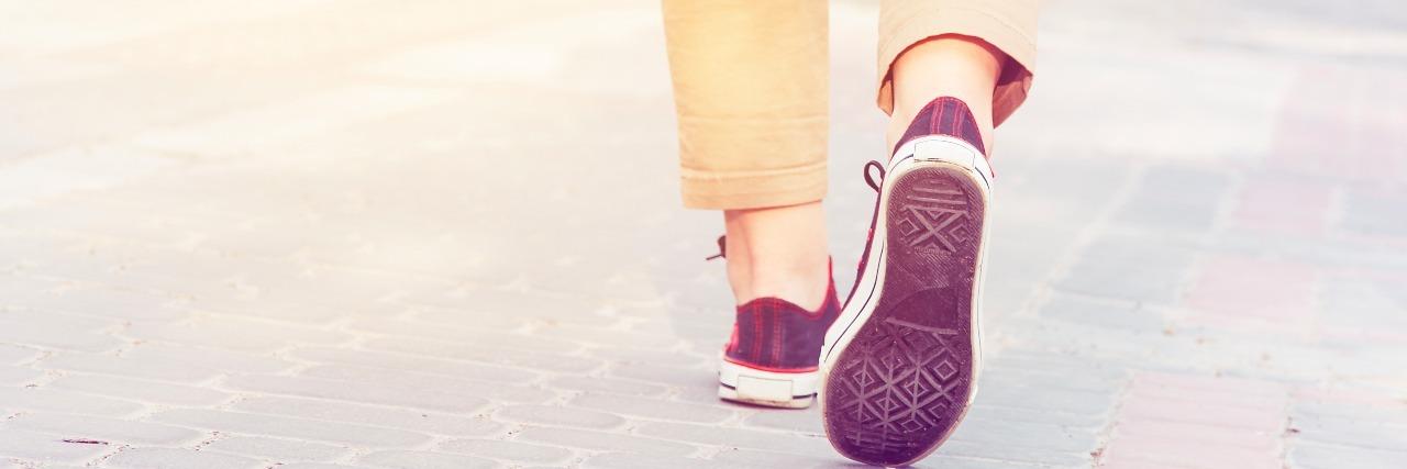 legs walking down street wearing pants and sneakers