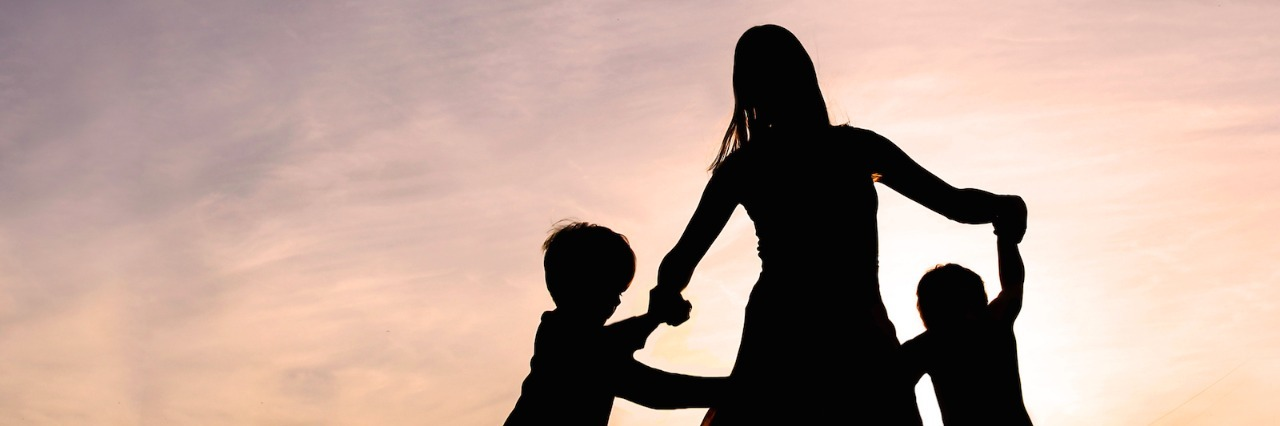 Silhouette of a woman and two young children holding hands and dancing around outside, isolated against the sunset.
