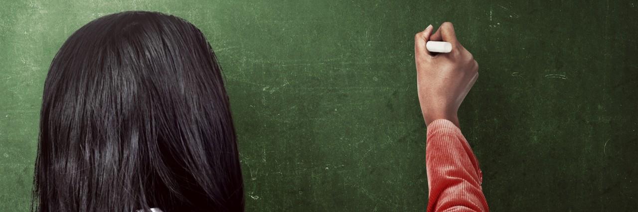woman drawing something on the blackboard