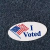 closeup of an american i voted sticker placed on a navy shirt
