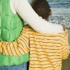 Mother and son with arms around each other, facing beach shoreline