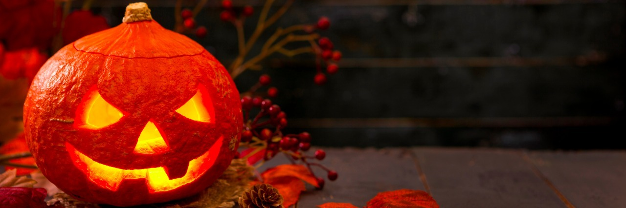 Burning Jack O'Lantern on a rustic table with autumn decorations