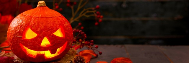 Burning Jack O'Lantern on a rustic table with autumn decorations, darkly lit.