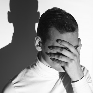 a young man covering his face with his hand