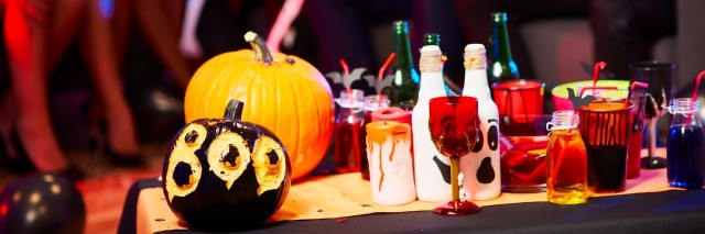 table at party with pumpkin and spooky drinks